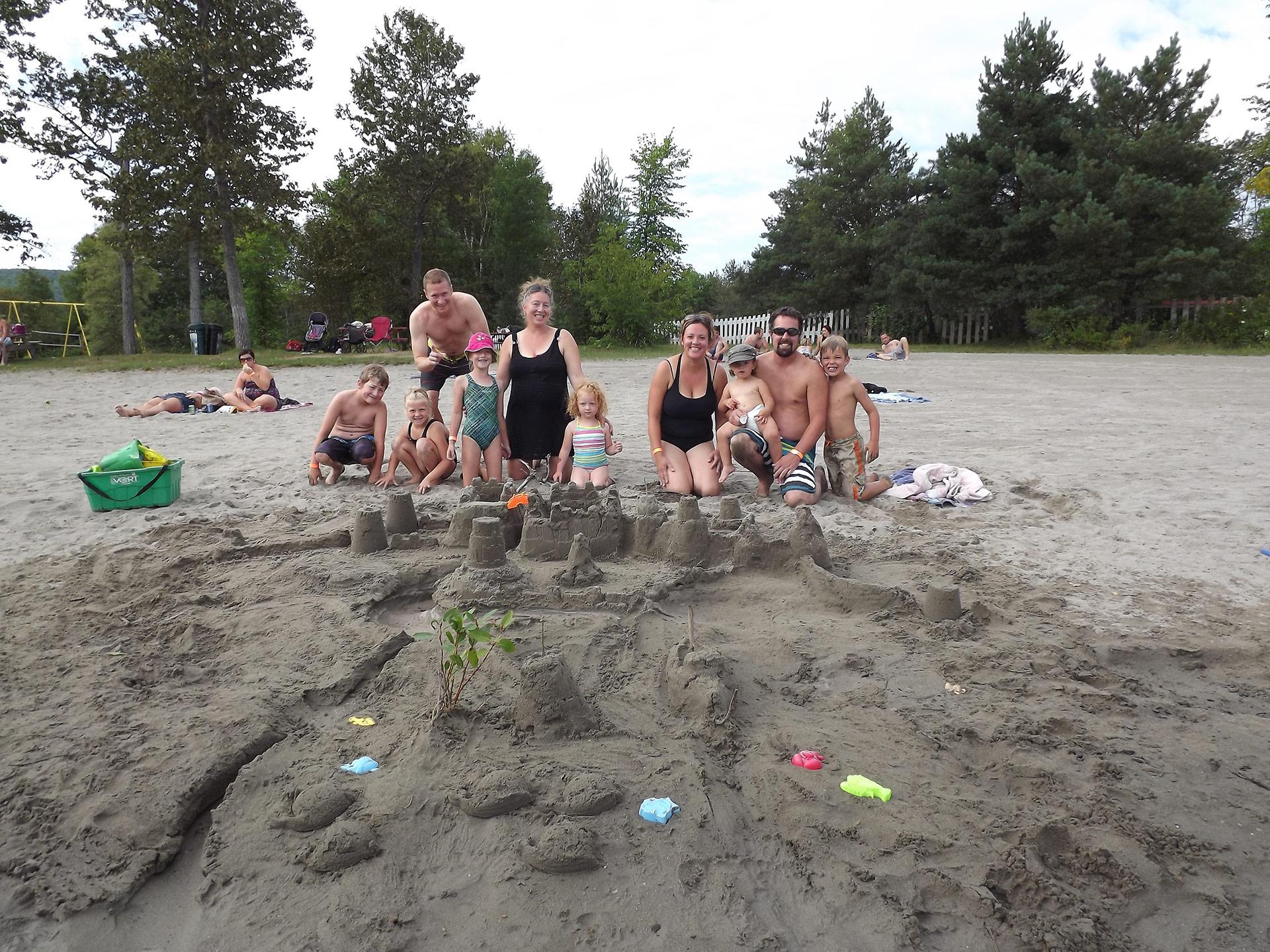 Une famille fait un chateau de sable sur la plage du lac Pohénégamook