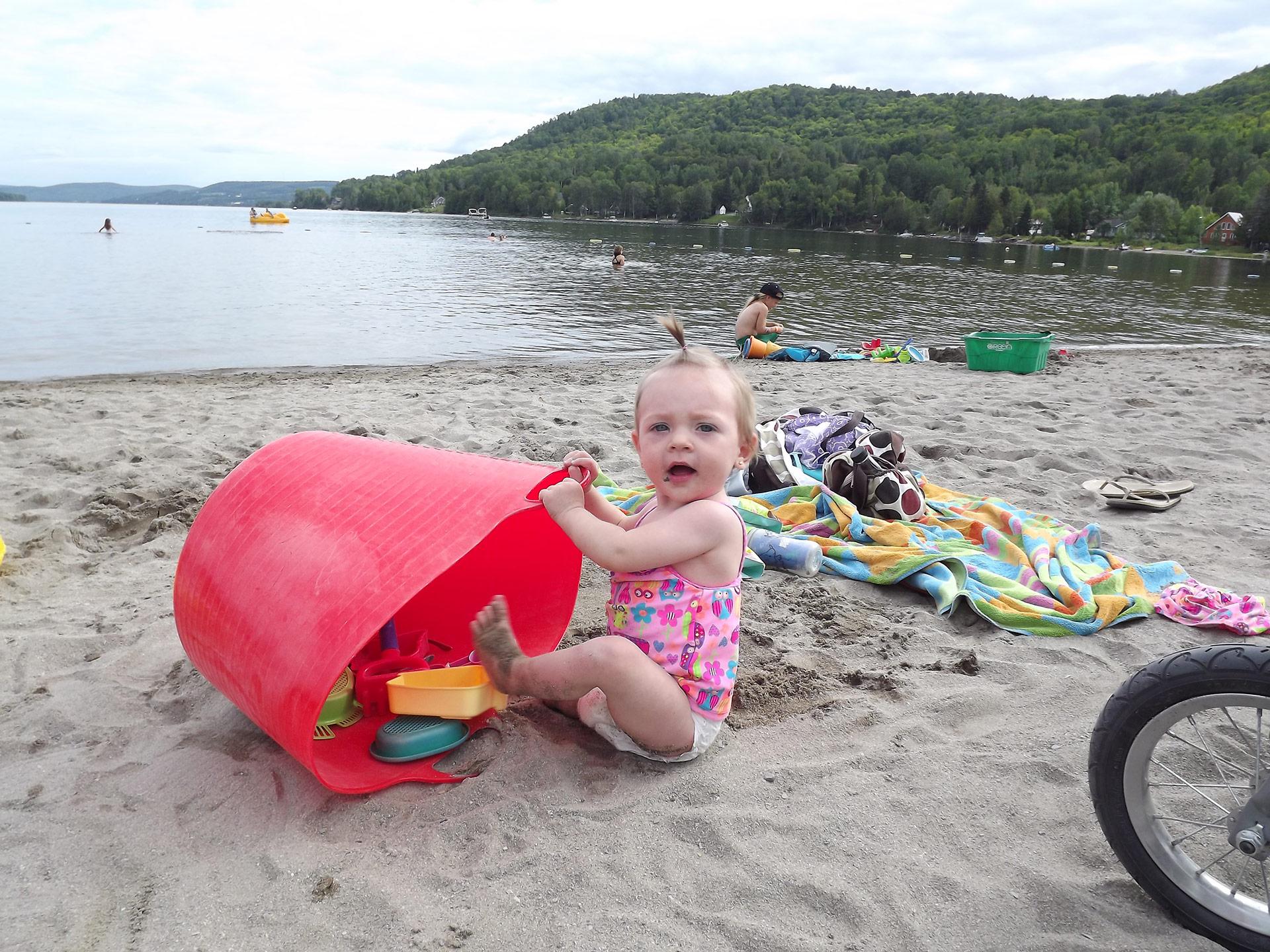 Un bébé joue sur la plage du lac Pohénégamook