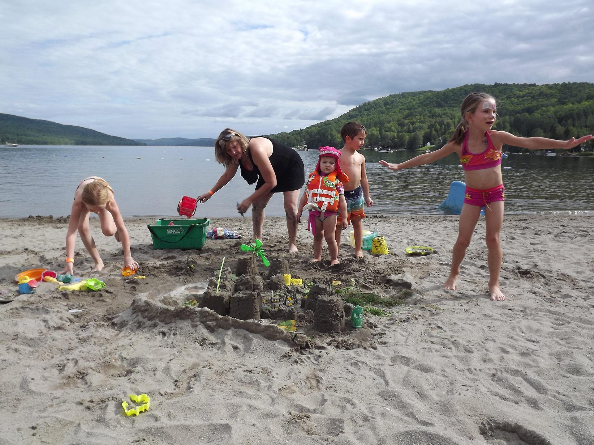 Des enfants jouent sur la plage du lac Pohénégamook